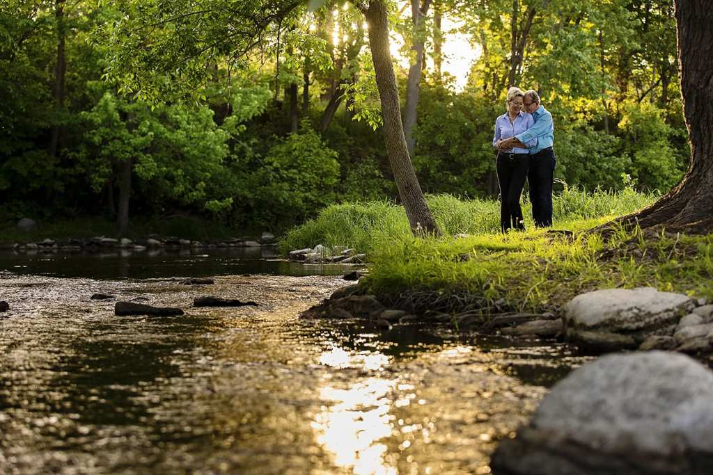 couple cuddling by stream for Williamstown engagement session