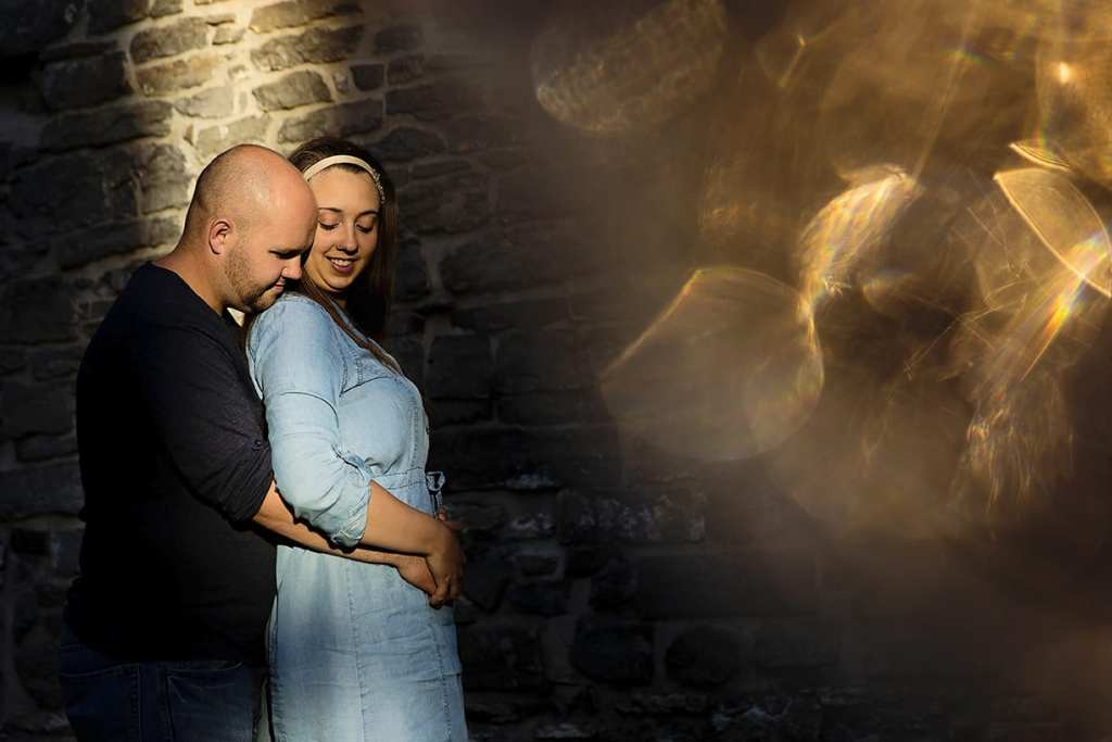 Couple cuddling in spotlight with wine glass bokeh during St Raphael's engagement session