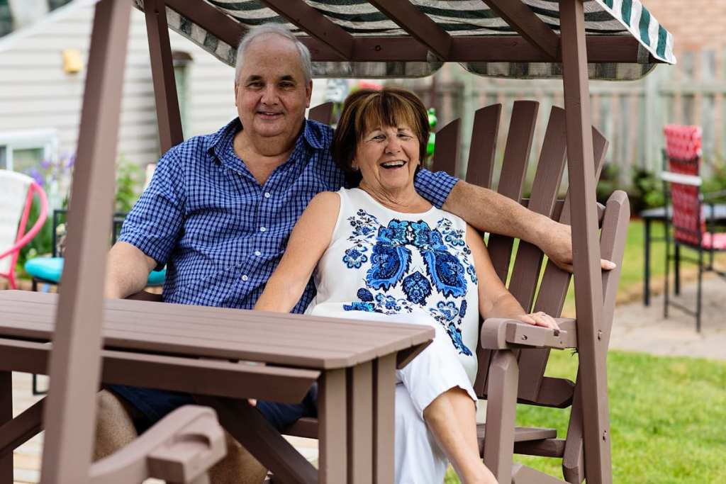 couple laughing on back yard swing during candid cornwall family photography session