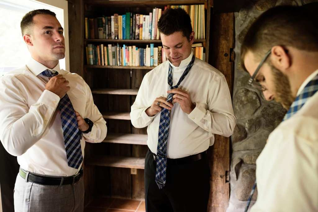 Groom and best man tying ties in country house library