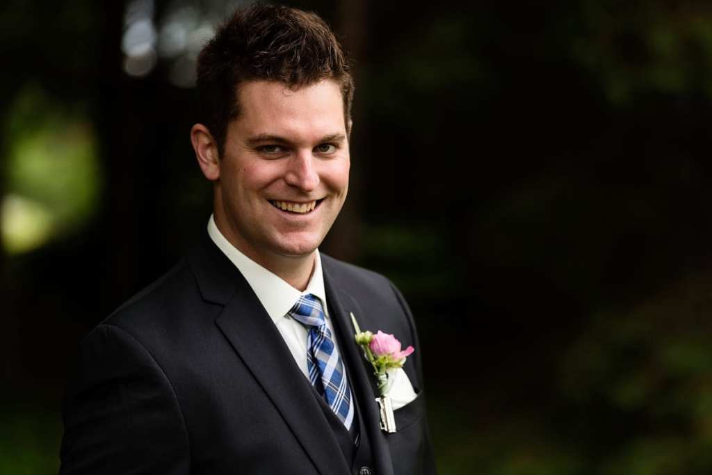 Groom in blue plaid tie with boutonniere