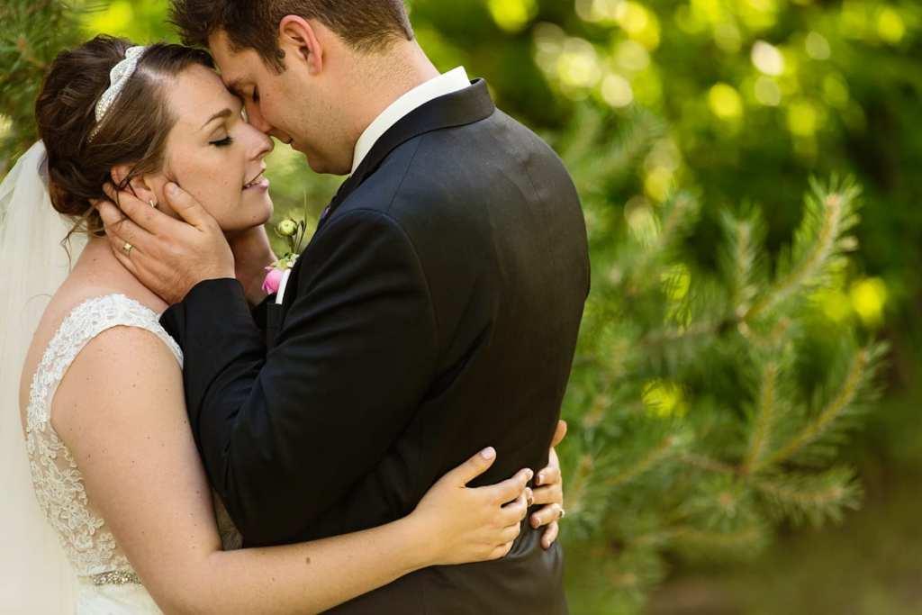 Bride and groom embracing in greenery in Williamstown wedding