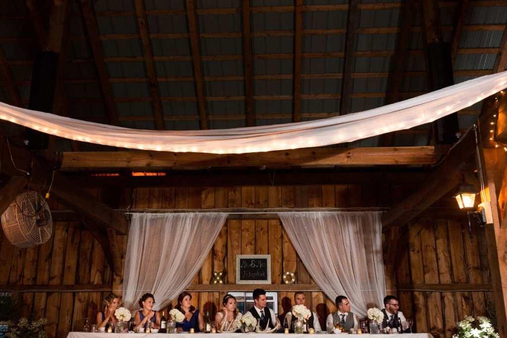 Head table with wedding party in rustic barn wedding venue