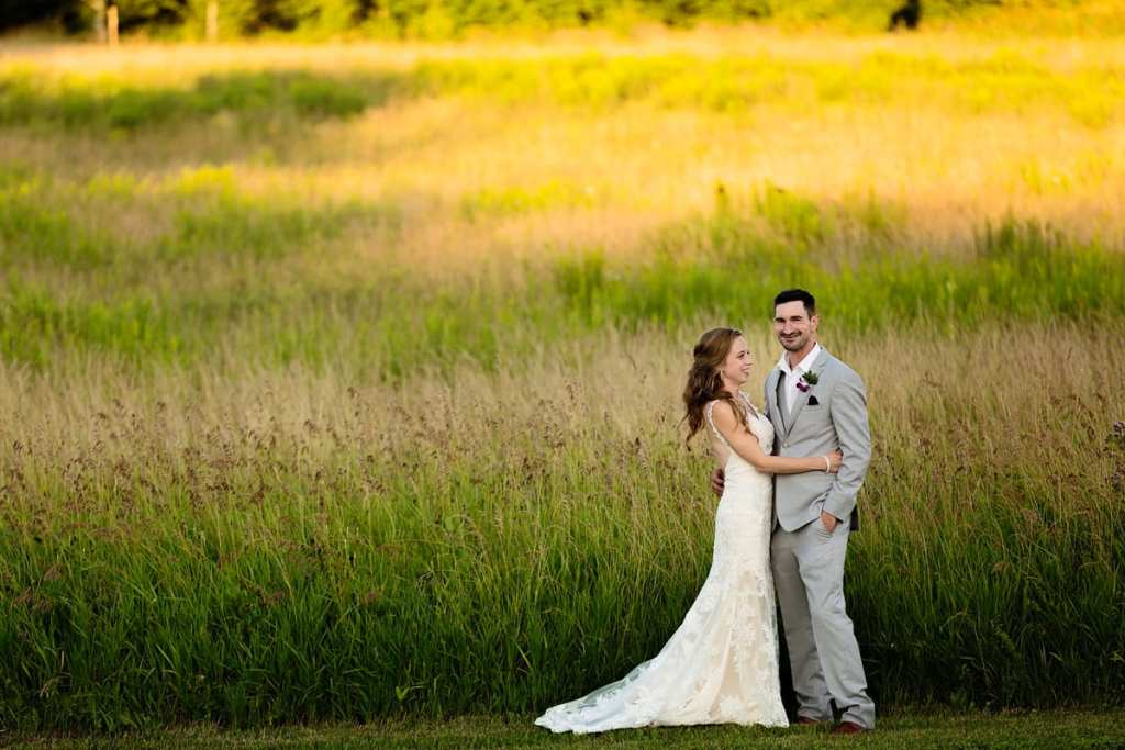 Bride and groom in field of tall grass at intimate Strathmere wedding