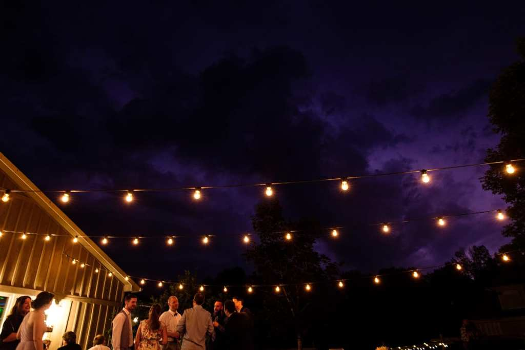 Wedding reception guests on outdoor patio under string lights and dramatic clouds with lightning