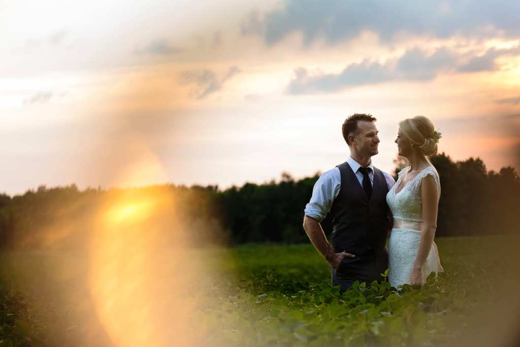 Bride and groom in tall green grass with sunburst