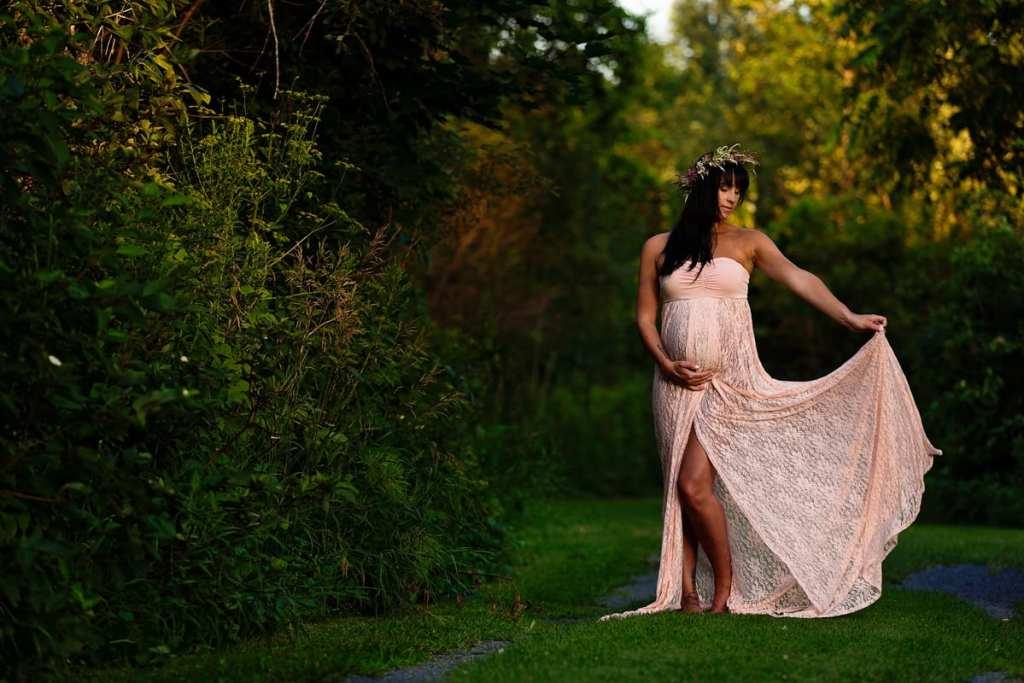 Bohemian pregnant woman in floral crown on lush green path