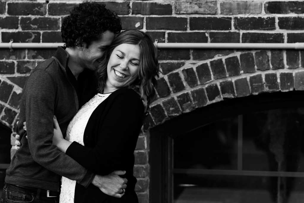 Couple laughing in front of brick building in urban Cornwall engagement session