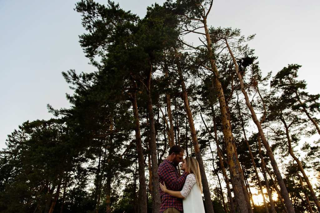 Man holding fiancee in front of tree stand in Rural Cornwall engagement session