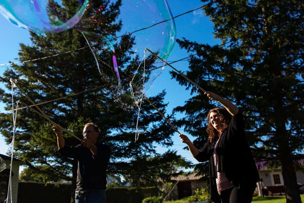 family making soap bubbles with large wands