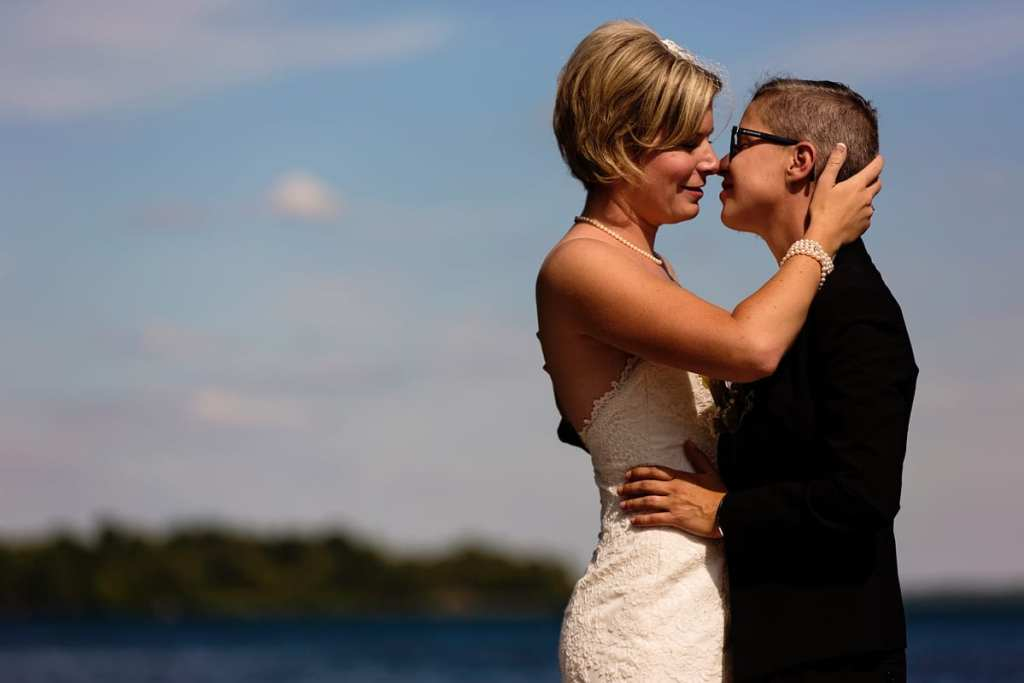 same-sex brides kissing in waterfront wedding shot