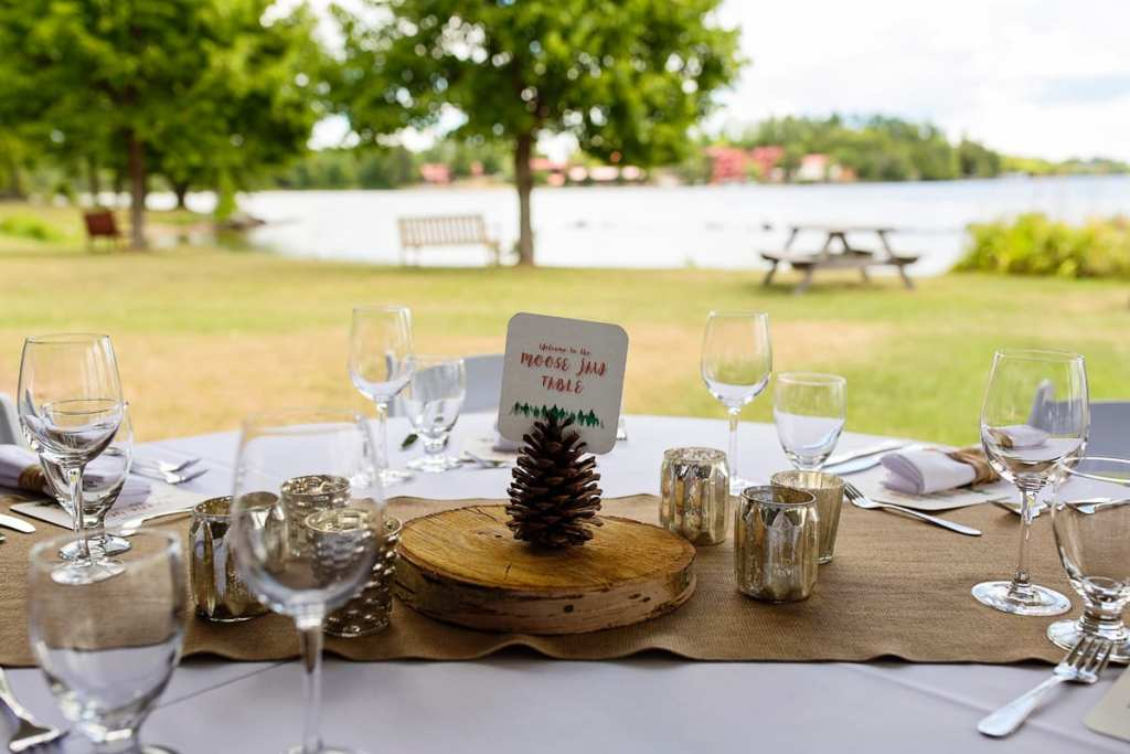 burlap rustic cut wood and pine cone centerpiece at lakeside wedding