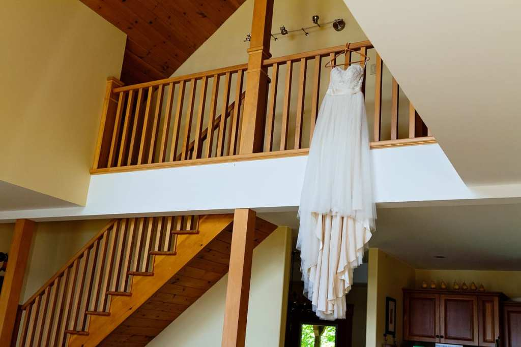 wedding dress hanging from balcony in rustic log cabin at Calabogie lake wedding