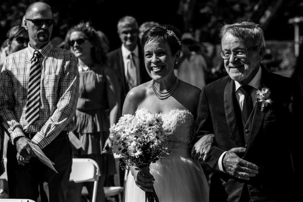smiling bride being walked down the aisle by her father