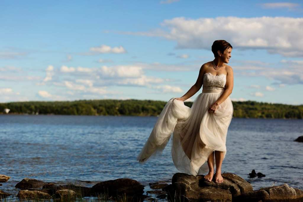 barefoot bride holding dress and standing on rock in Calabogie lake