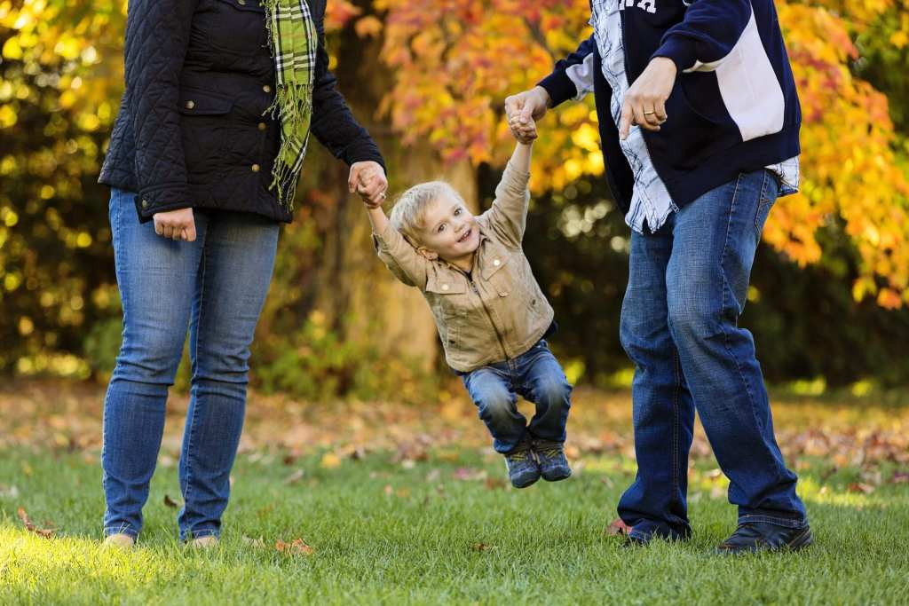 parents swinging young smiling boy in rural family photo shoot