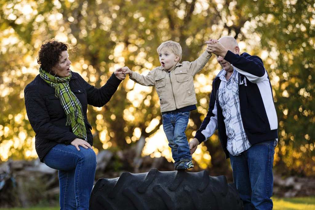 son playing with parents on tractor tires in rural fall family session