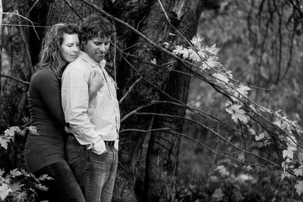 woman embracing fiance beside large tree in black and white fall engagement photo
