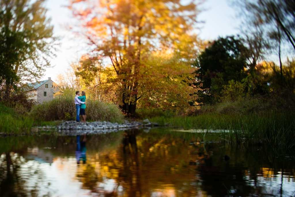 Couple standing beside reflection in water with fall trees and mill