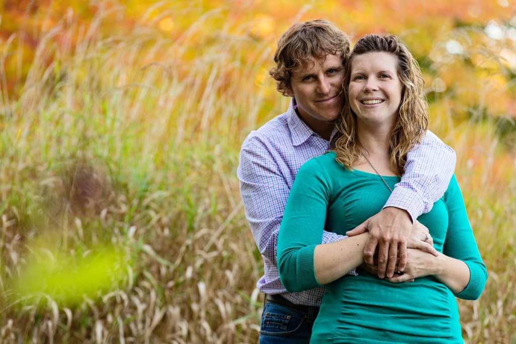 man embracing fiancee in tall grass field in fall rural engagement session