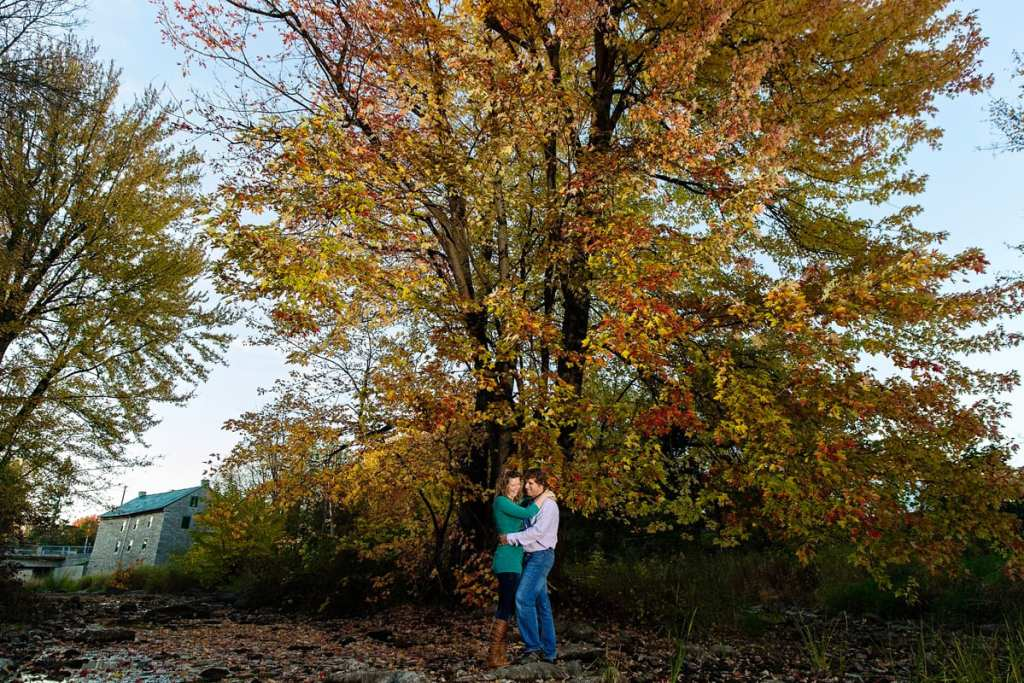 couple embracing in fall scene with Martintown mill in background