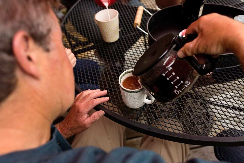 dad pouring coffee and baileys for family on log cabin patio