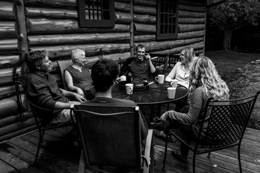 family sharing laughs and coffee at outdoor patio table of log cabin during Ontario Casual Family Portraits