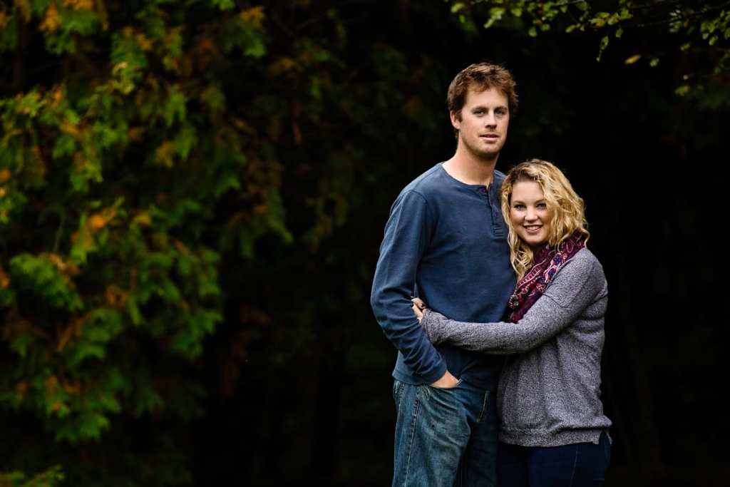 young smiling couple in front of dark green leafy background