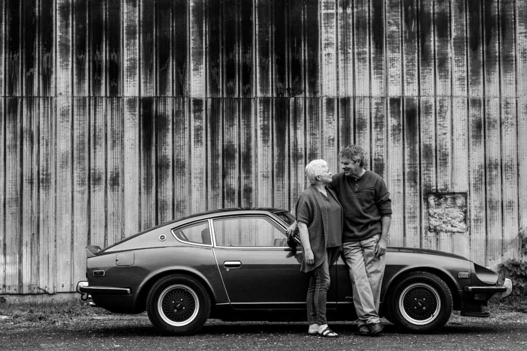 mature couple with rustic building background and classic car