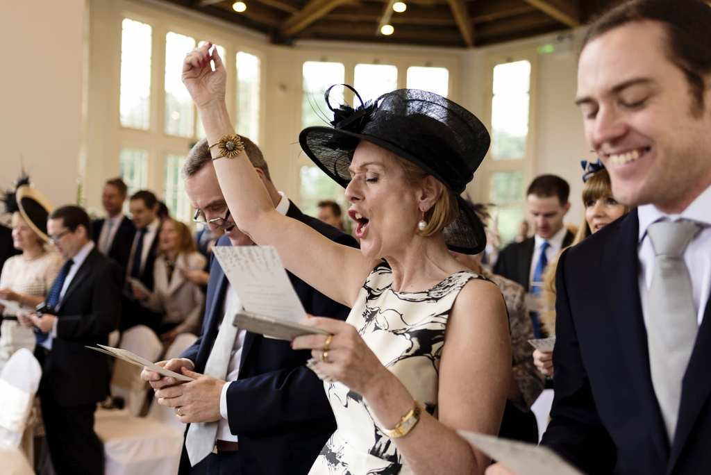 mother of the bride sings enthusiastically during Highcliffe Castle wedding ceremony