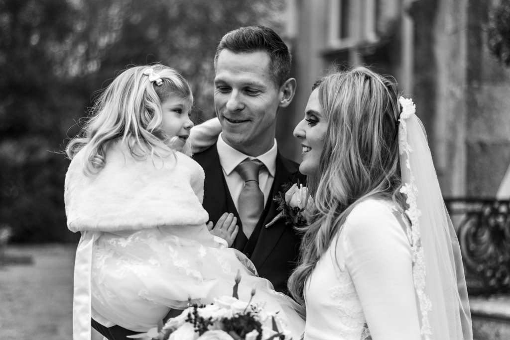bride and groom with flower girl in groom's arms after Highcliffe Castle wedding ceremony