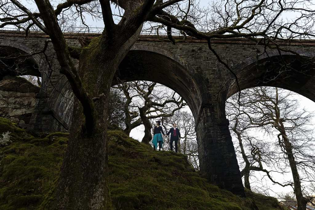 man and woman look opposite directions while standing under a viaduct during Snowdonia portrait session