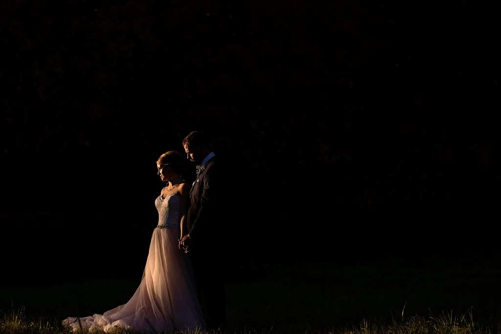 bride in blush gown faces sun with groom behind her during Autumnal NAV Centre Cornwall Wedding