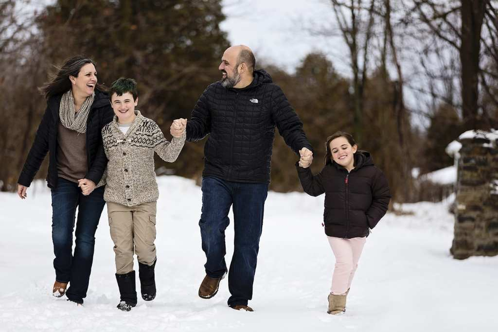 parents hold hands with two children while they skip in the snow