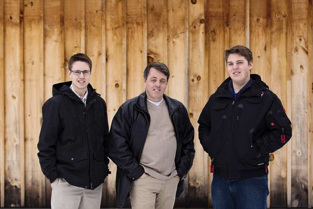 man stands in front of raw wood wall with two sons all in black jackets