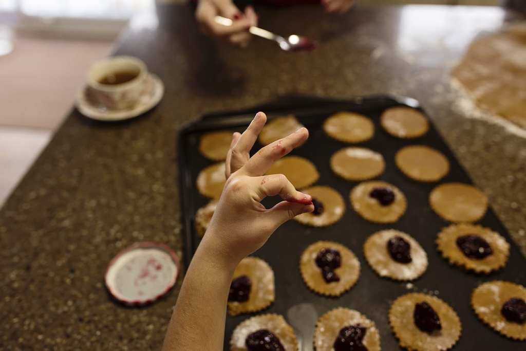 sticky jam fingers make okay sign while baking cookies