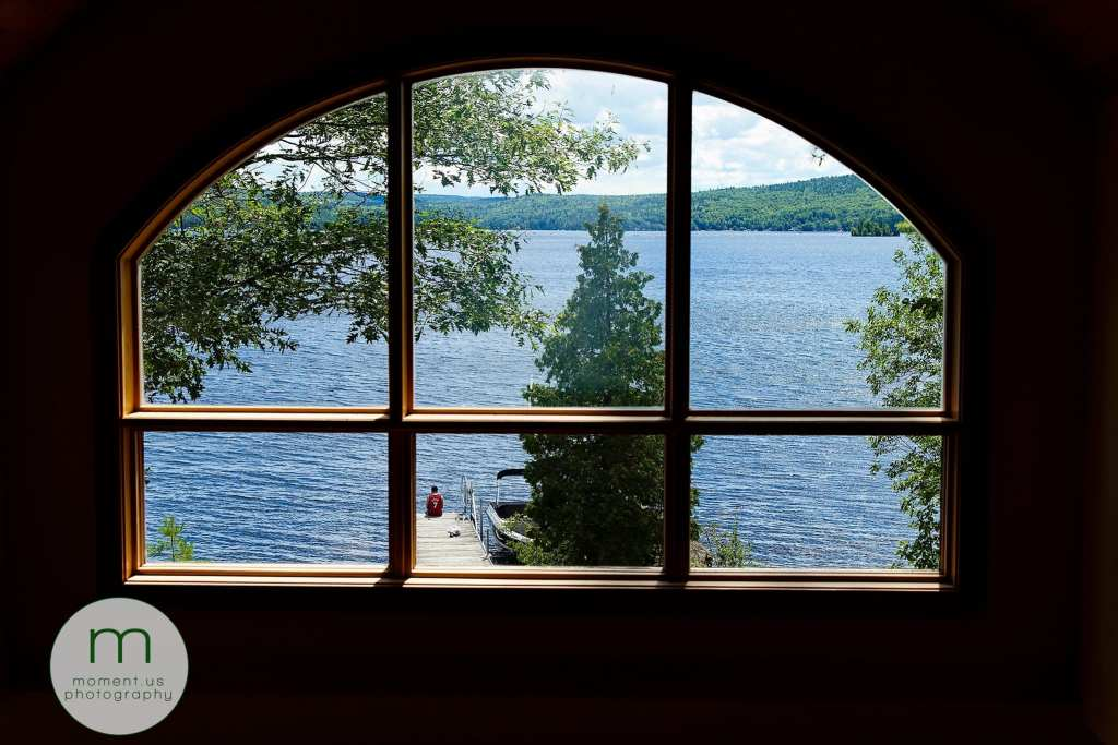 Man sits at end of dock surrounded by trees and framed in large semi-circular window