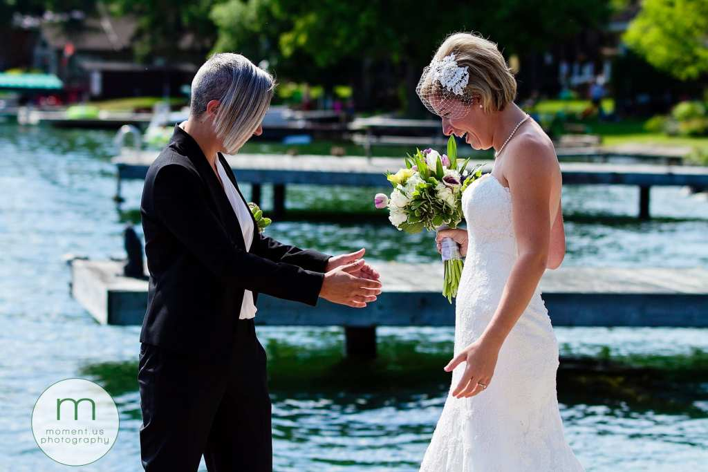brides see each other for first time during waterfront Cornwall gay wedding first look
