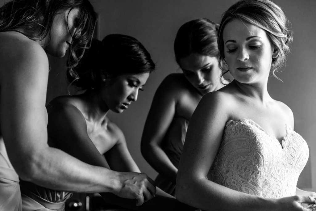 bride looks over shoulder while bridesmaids fasten her dress for Autumnal NAV Centre Cornwall Wedding