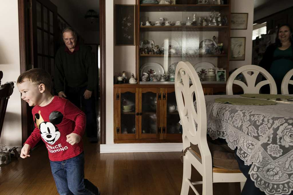 boy runs from grandpa during Ontario Family Photojournalism session