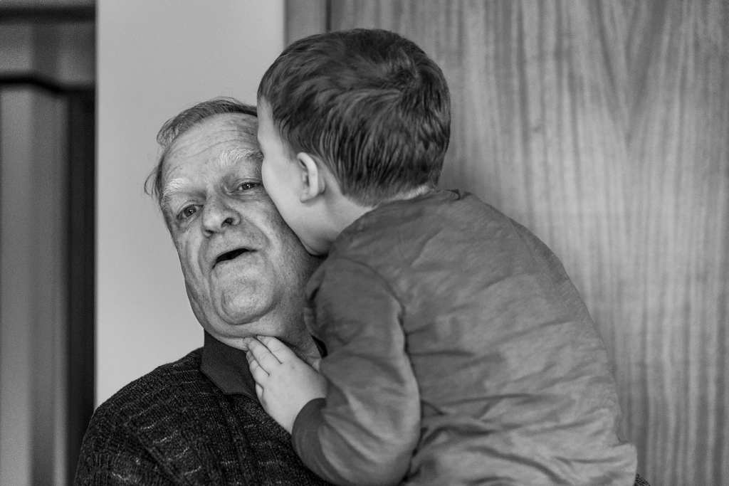 boy bites grandpa's face during Ontario Family Photojournalism session