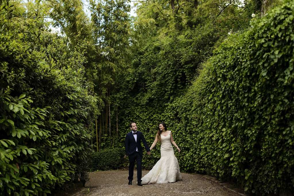 bride and groom walk up driveway surrounded by hedges during session with Ontario & Destination Wedding Photographer