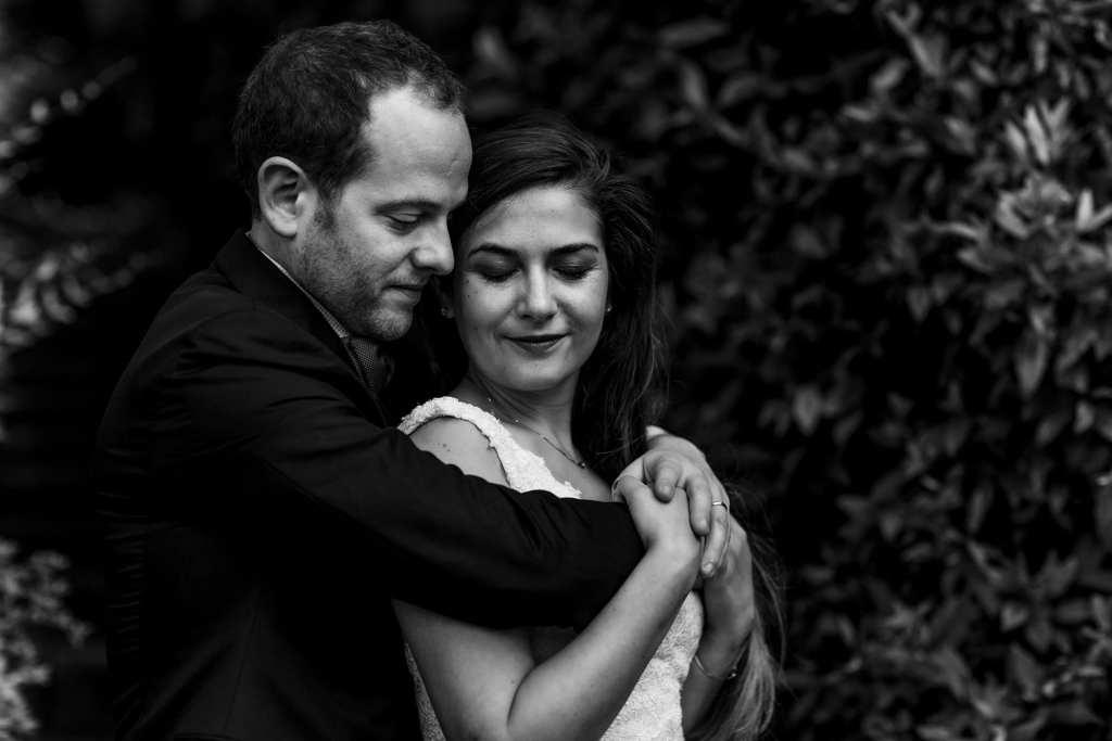 groom wraps arms around bride's shoulders