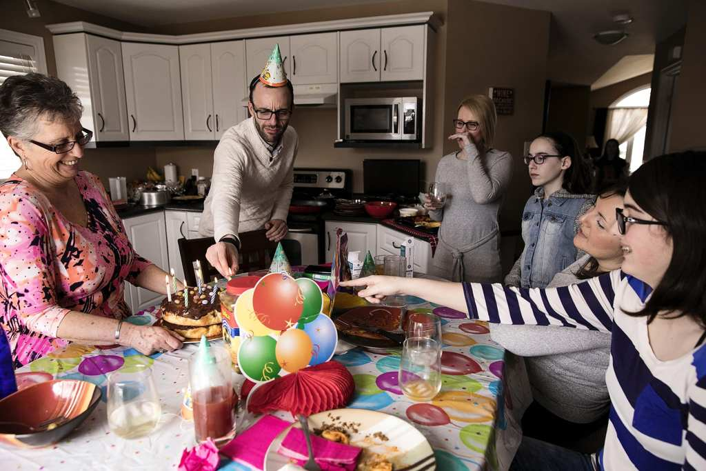 family members gathered around table each pointing differently