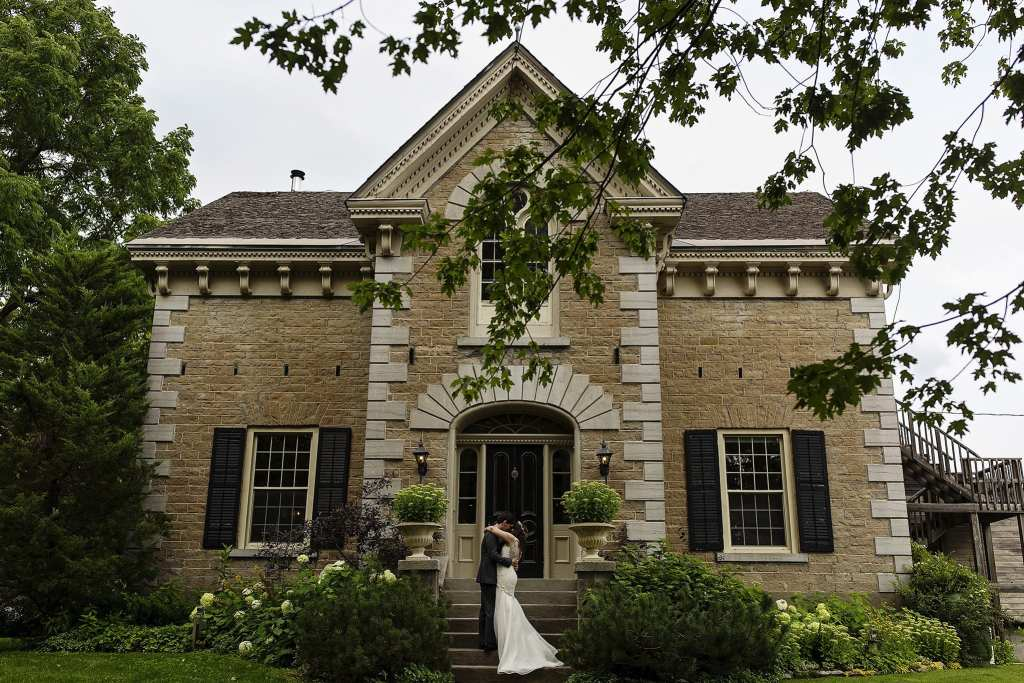 bride and groom embrace during first look on front steps of Strathmere Inn