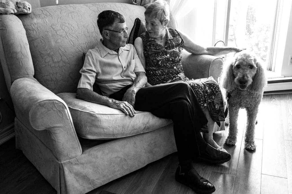 wife looks at husband while petting dog during documentary anniversary session