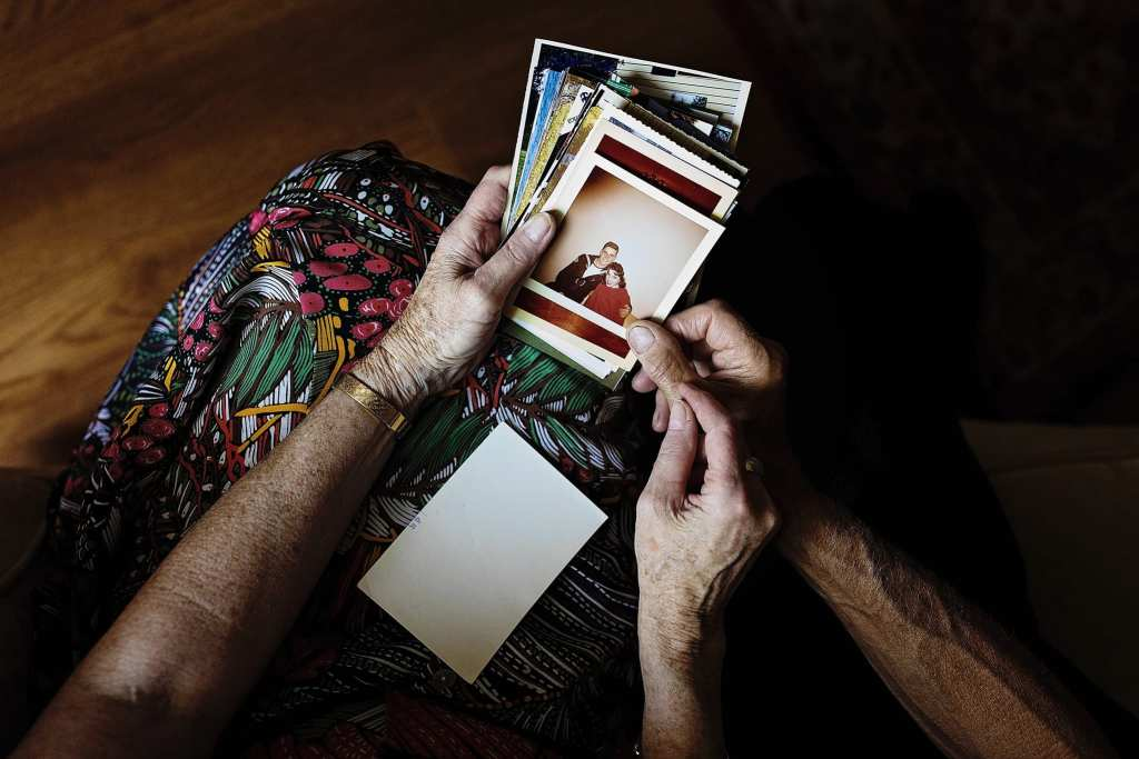 husband and wife hold stack of old photographs during documentary anniversary session