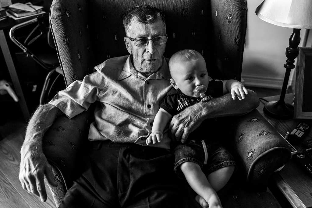 grandpa holds grandson while sitting in wingback chair