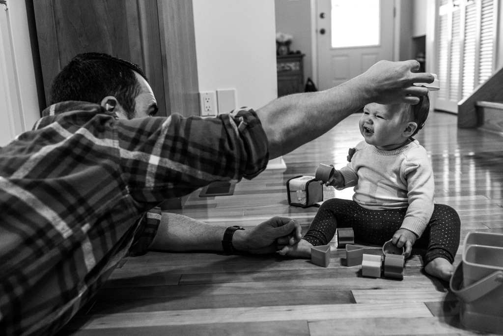 dad puts toy on daughter's head while playing on kitchen floor