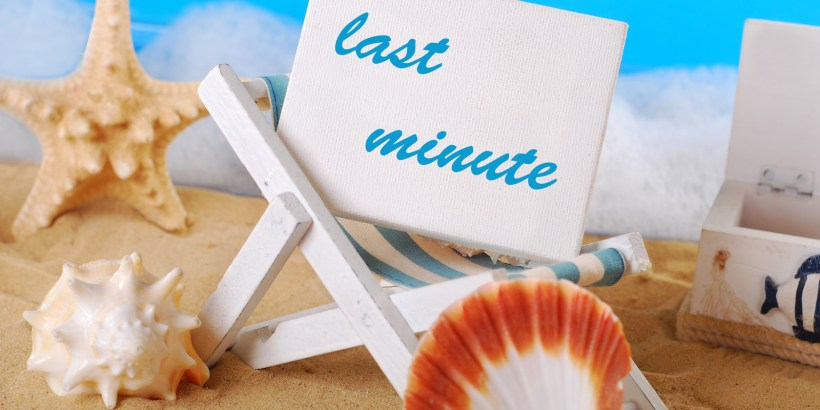 "white board with text ""last minute"" standing on wooden deckchair on the beach"